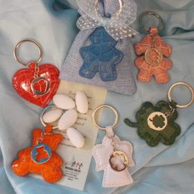 cod.PCH300 Portachiavi similpelle su sacchettino - 6 soggetti a scelta - oresetto-cuore-angioletto-quadrifoglio-bimbo-bimba