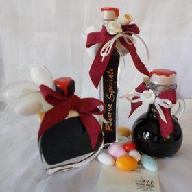 Bottiglie in vetro trasparente contenente  balsamico di Modena, con tappo in sughero e sigillo in cera lacca. Disponibili nella forma a cuore, rettangolare, o anfora con manico